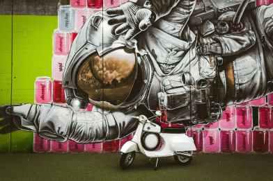 white motor scooter parked near graffiti wall